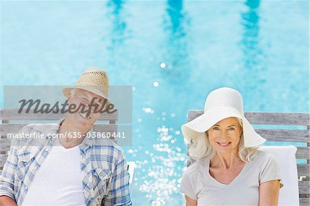 Senior couple wearing sun hats at poolside Stock Photo - Premium Royalty-Free, Image code: 635-03860441