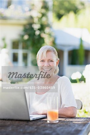 Woman using laptop at patio table Stock Photo - Premium Royalty-Free, Image code: 635-03860459