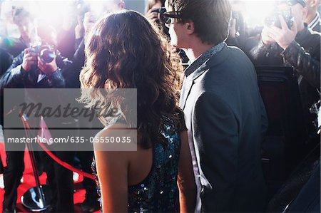 Celebrities posing for paparazzi on red carpet Stock Photo - Premium Royalty-Free, Image code: 635-05550035