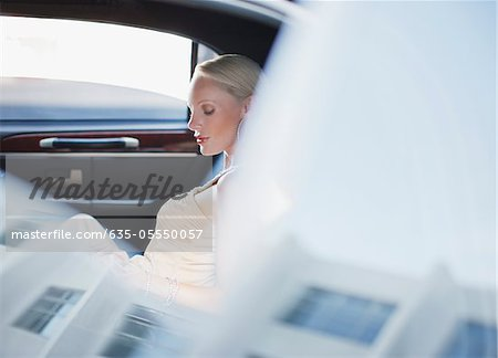 Woman sitting in backseat of limo Stock Photo - Premium Royalty-Free, Image code: 635-05550057