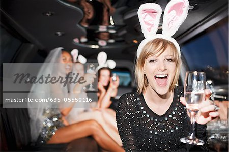 Woman in bunny ears drinking champagne in limo Stock Photo - Premium Royalty-Free, Image code: 635-05550116