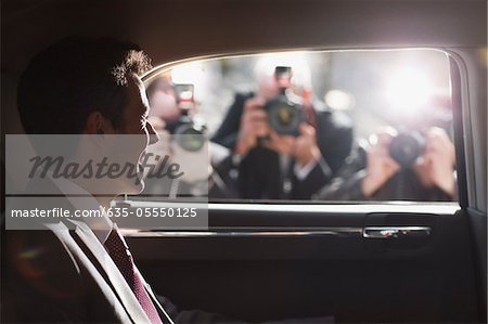 Politician smiling for paparazzi in backseat of car Stock Photo - Premium Royalty-Free, Image code: 635-05550125