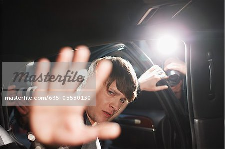 Celebrity blocking photo in backseat of limo Stock Photo - Premium Royalty-Free, Image code: 635-05550130
