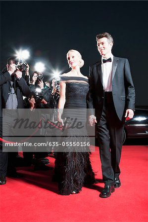 Celebrities posing for paparazzi on red carpet Stock Photo - Premium Royalty-Free, Image code: 635-05550156