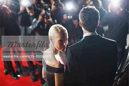 Celebrities posing for paparazzi on red carpet Stock Photo - Premium Royalty-Free, Image code: 635-05550171