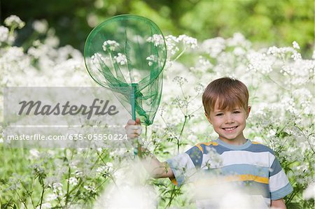 Boy playing with butterfly net in field of flowers Stock Photo - Premium Royalty-Free, Image code: 635-05550224
