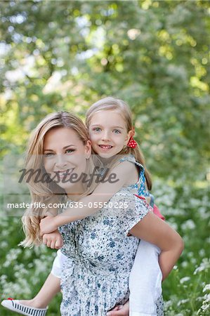 Mother carrying daughter outdoors Stock Photo - Premium Royalty-Free, Image code: 635-05550225