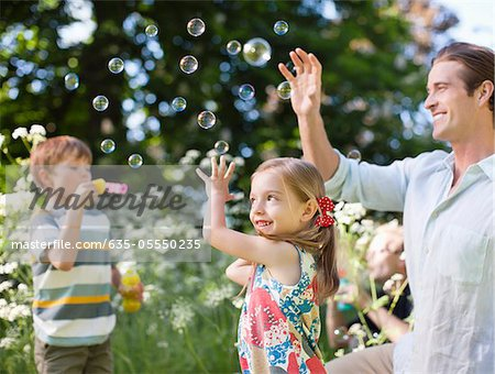 Family playing with bubbles in park Stock Photo - Premium Royalty-Free, Image code: 635-05550235