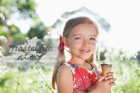 Girl eating ice cream outdoors Stock Photo - Premium Royalty-Free, Image code: 635-05550237