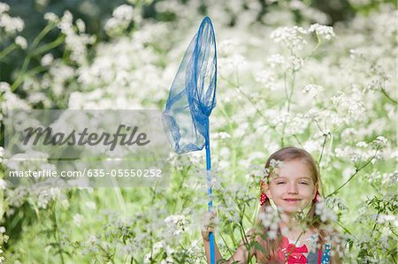 Girl playing with butterfly net in field of flowers Stock Photo - Premium Royalty-Free, Image code: 635-05550252