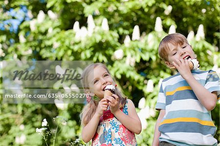 Children licking ice cream outdoors Stock Photo - Premium Royalty-Free, Image code: 635-05550270