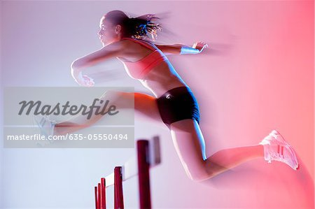 Blurred view of runner jumping hurdles Stock Photo - Premium Royalty-Free, Image code: 635-05550494