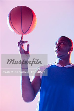 Basketball player balancing ball on one finger