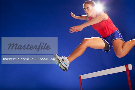 Athlete jumping over hurdles Stock Photo - Premium Royalty-Free, Image code: 635-05550564