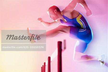 Blurred view of athlete jumping hurdles Stock Photo - Premium Royalty-Free, Image code: 635-05550574