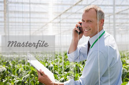 Businessman talking on cell phone in greenhouse Stock Photo - Premium Royalty-Free, Image code: 635-05550712