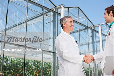 Scientists shaking hands outside greenhouse Stock Photo - Premium Royalty-Free, Image code: 635-05550774
