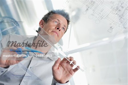 Architect drawing on glass table Stock Photo - Premium Royalty-Free, Image code: 635-05550853