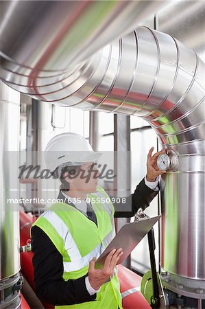 Businessman checking gauges on pipes in factory Stock Photo - Premium Royalty-Free, Image code: 635-05550908