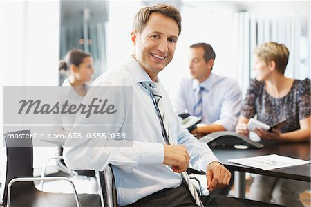 Businessman smiling at conference desk Stock Photo - Premium Royalty-Free, Image code: 635-05551058