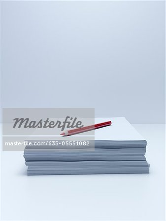 Red pencil on stack of paper Stock Photo - Premium Royalty-Free, Image code: 635-05551082