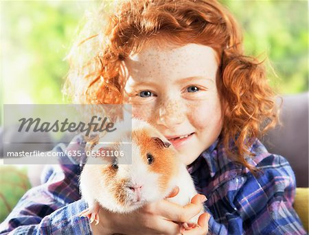 Girl holding pet hamster in living room Stock Photo - Premium Royalty-Free, Image code: 635-05551106