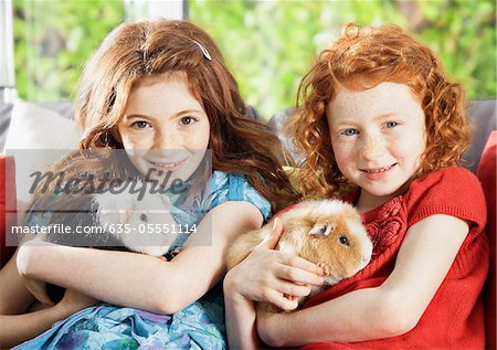 Girls holding pet hamsters in living room Stock Photo - Premium Royalty-Free, Image code: 635-05551114