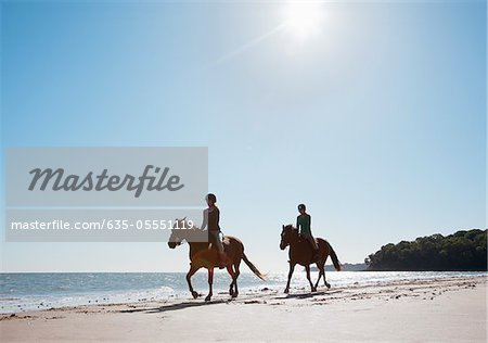 Girls riding horses on beach Stock Photo - Premium Royalty-Free, Image code: 635-05551119