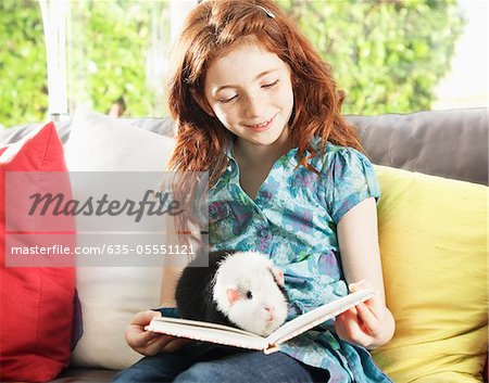 Girl reading with pet hamster Stock Photo - Premium Royalty-Free, Image code: 635-05551121