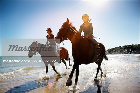 Girls riding horses on beach Stock Photo - Premium Royalty-Free, Image code: 635-05551122