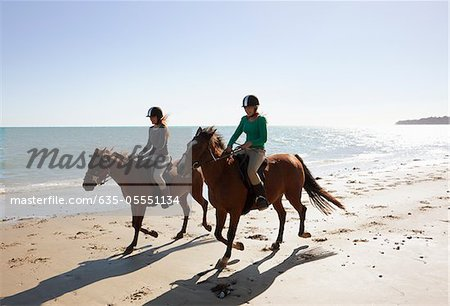 Girls riding horses on beach Stock Photo - Premium Royalty-Free, Image code: 635-05551134