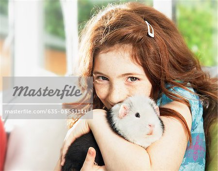 Girl hugging pet hamster Stock Photo - Premium Royalty-Free, Image code: 635-05551141