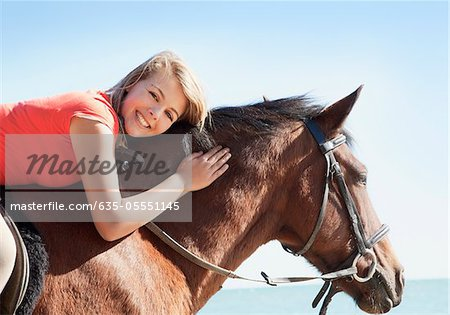 Girl petting horse on beach Stock Photo - Premium Royalty-Free, Image code: 635-05551145