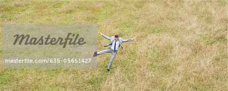 Businessman jumping in field Stock Photo - Premium Royalty-Free, Image code: 635-05651427