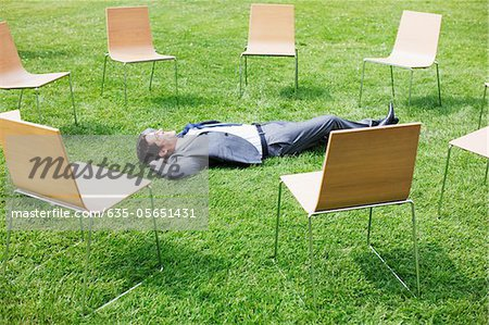 Businessman laying in grass surrounded by chairs Stock Photo - Premium Royalty-Free, Image code: 635-05651431