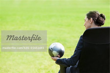 Businesswoman sitting outdoors holding globe