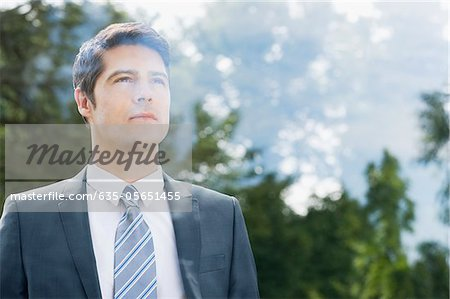Businessman looking through window Stock Photo - Premium Royalty-Free, Image code: 635-05651455