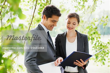 Business people looking at report together outdoors Stock Photo - Premium Royalty-Free, Image code: 635-05651468
