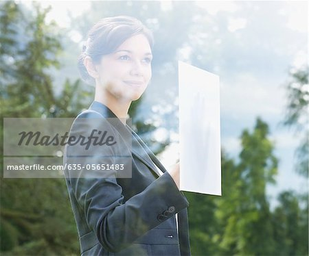 Businesswoman holding paper against window Stock Photo - Premium Royalty-Free, Image code: 635-05651483
