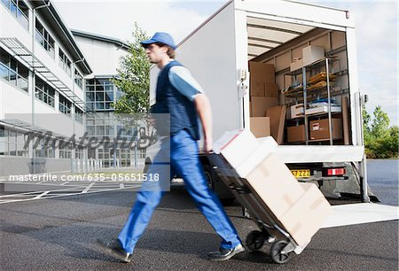 Deliveryman puling boxes on hand truck Stock Photo - Premium Royalty-Free, Image code: 635-05651518