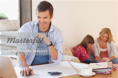 Man working with family in background Stock Photo - Premium Royalty-Free, Image code: 635-05651522