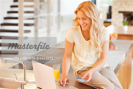 Woman shopping online with credit card Stock Photo - Premium Royalty-Free, Image code: 635-05651531