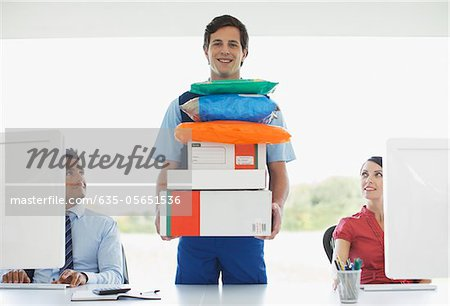 Deliveryman holding stack of packages in office Stock Photo - Premium Royalty-Free, Image code: 635-05651536
