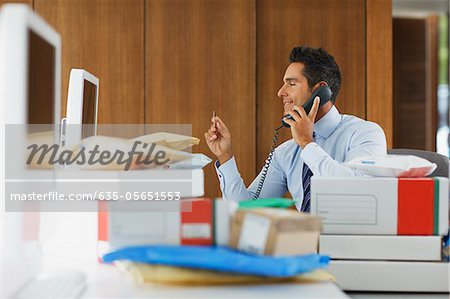 Businessman talking on telephone behind packages Stock Photo - Premium Royalty-Free, Image code: 635-05651553