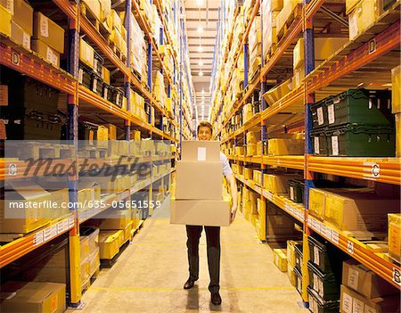 Worker carrying boxes in warehouse Stock Photo - Premium Royalty-Free, Image code: 635-05651559