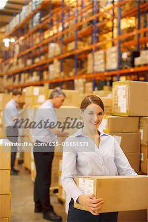 Workers packing boxes in warehouse Stock Photo - Premium Royalty-Free, Image code: 635-05651571