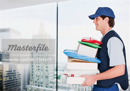 Deliveryman carrying stack of packages Stock Photo - Premium Royalty-Free, Image code: 635-05651577