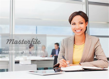 Businesswoman working at desk in office Stock Photo - Premium Royalty-Free, Image code: 635-05651586