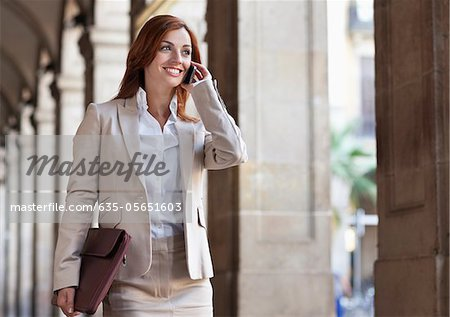 Businesswoman walking outdoors talking on cell phone