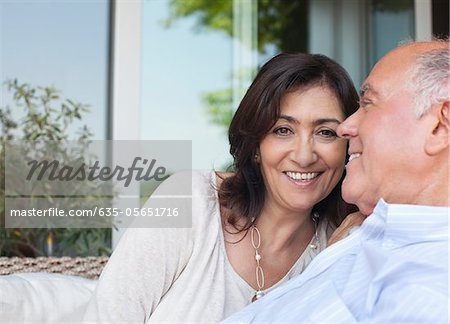 Smiling couple sitting together outdoors Stock Photo - Premium Royalty-Free, Image code: 635-05651716
